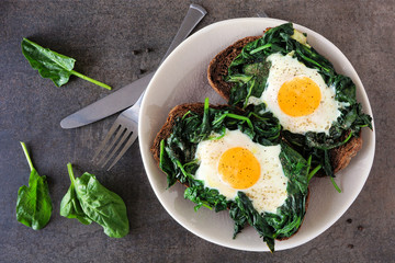Healthy toasts with spinach and egg on a plate. Above view over a dark stone background.