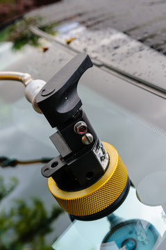 Autoglass professional repair to a chipped windscreen using vacuum pump and resin, with mirror placed behind to view repair