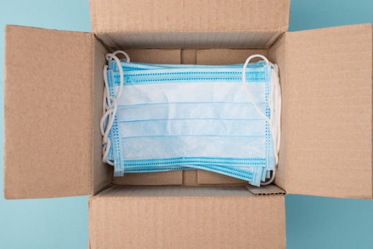 Humanitarian aid help concept. Top above overhead close up view photo of open unpacked unwrapped box with lot of medical masks on blue background