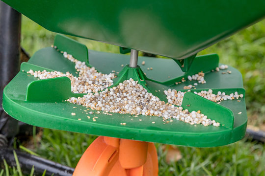 Closeup of lawn fertilizer spreader with granules of weed killer herbicide, urea nitrogen and potash