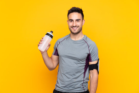 Sport man over isolated yellow wall with sports water bottle