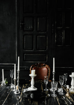 On a black wooden table are cutlery and white candlesticks. Against the background of black doors . Photozone . Gothic wedding table decoration