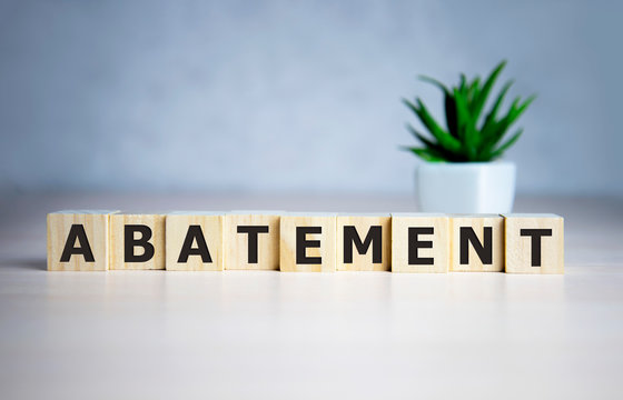The word ABATEMENT written on wooden cubes on a blue background