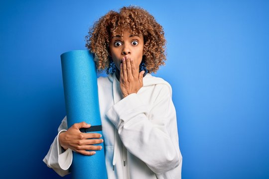 Young african american woman doing sport holding yoga mat over isolated blue background cover mouth with hand shocked with shame for mistake, expression of fear, scared in silence, secret concept