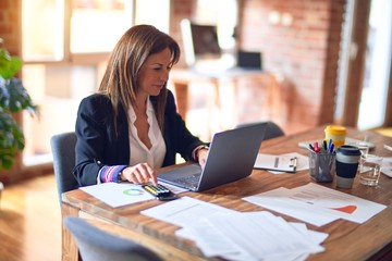 Middle age beautiful businesswoman smiling happy and confident. Sitting on chair working in a desk using laptop at the office