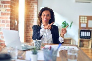 Middle age beautiful businesswoman working using laptop at the office smiling and looking at the camera pointing with two hands and fingers to the side.