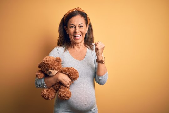 Middle age pregnant woman expecting baby holding teddy bear stuffed animal screaming proud and celebrating victory and success very excited, cheering emotion