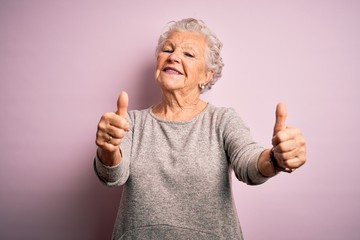 Senior beautiful woman wearing casual t-shirt standing over isolated pink background approving doing positive gesture with hand, thumbs up smiling and happy for success. Winner gesture.