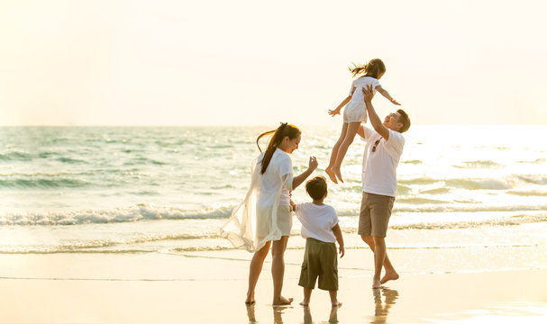 Happy Young Asian happy family parents with child walking and having fun together on the beach at sunset in summertime. Father, mother and kids relax and enjoy summer lifestyle travel holiday vacation