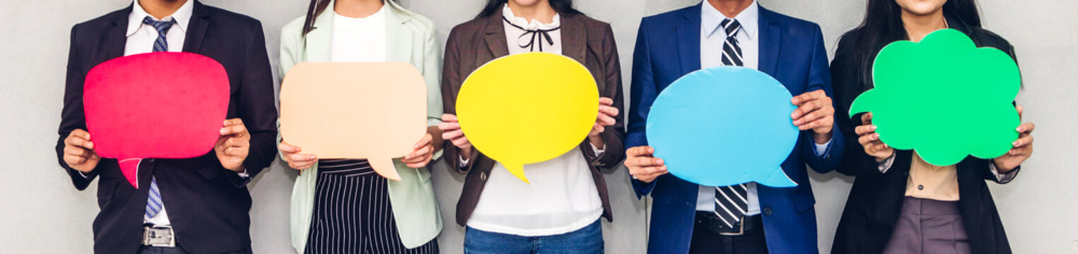 Group of business people holding a empty copyspace speech bubble icon while standing against grey background