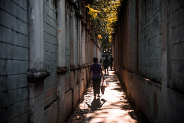 Photo sur Aluminium Ruelle etroite The sun shines through a narrow alley that is surrounded by people.