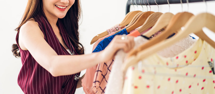Beautiful young asia woman shopping and choosing clothes in a store.fashion shopping concept