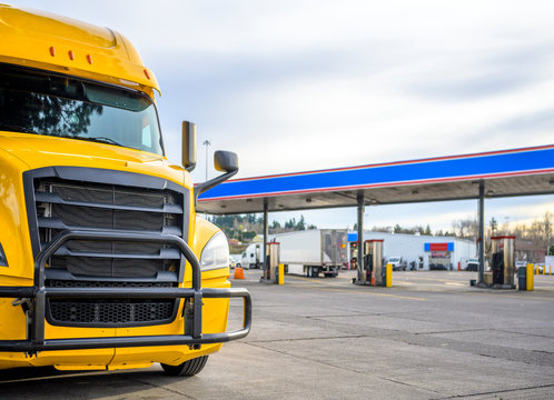 Yellow big rig semi truck with grille guard standing on the truck stop with fuel station on the parking lot