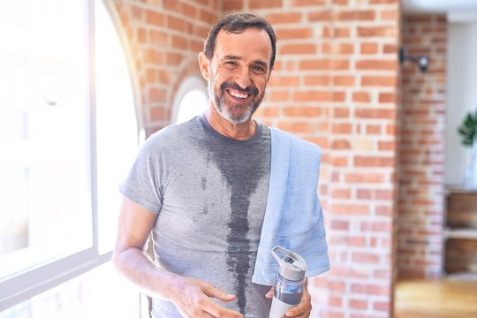 Middle age handsome sportman sweaty holding bottle of water and towel after exercise at gym with a happy face standing and smiling with a confident smile showing teeth