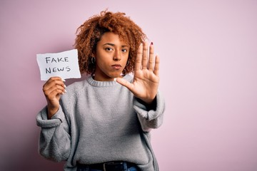 Young African American afro woman with curly hair holding paper with fake news message with open hand doing stop sign with serious and confident expression, defense gesture