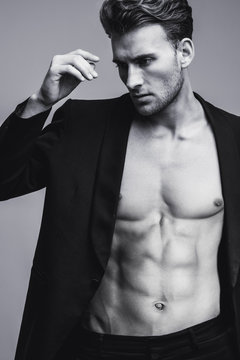 Black and white portrait of handsome young man with stylish haircut in the black suit. Perfect body & skin. Close up. Studio shot