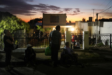 People queue for free dinner made by the Salazar family who cooked for their neighbours, many of whom have lost their jobs as a consequence of the coronavirus disease (COVID-19), in Montevideo