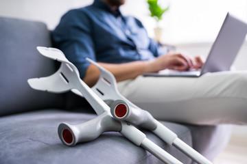 Man With Leg Injury Using Laptop