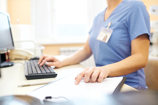 Close-up of unrecognizable nurse sitting at desk and using computer while analyzing medical notes