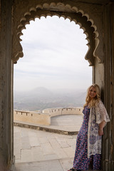 Woman tourist stands at an arched doorway, posing at the Monsoon Palace in Udaipur, India