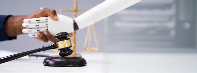 Gavel With Man And Robot Shaking Hands