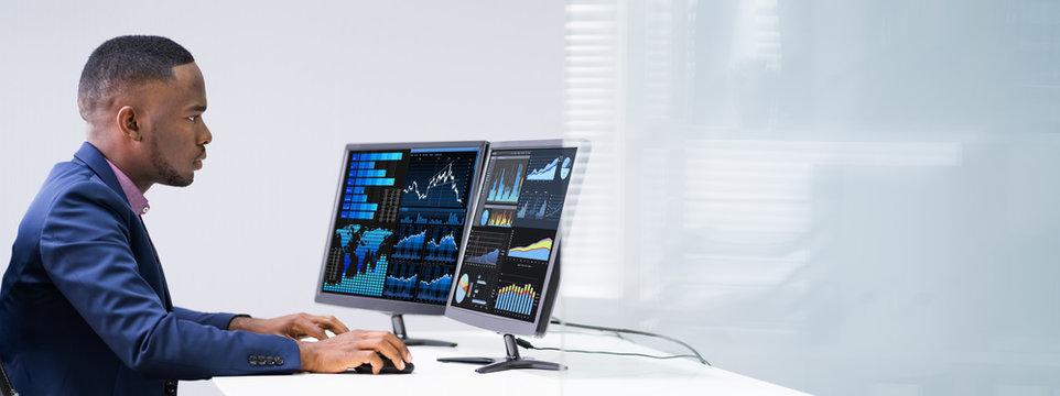Stock Market Broker Analyzing Graphs On Laptop