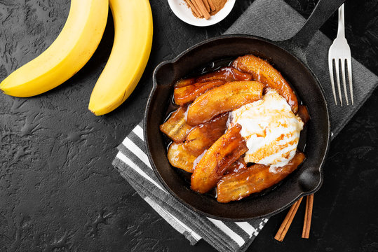 Homemade fried bananas foster with cinnamon and ice cream in cast iron pan
