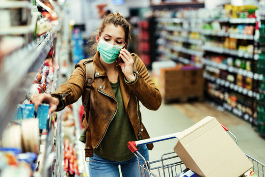 Woman with face mask talking on the phone while shopping in grocery store.