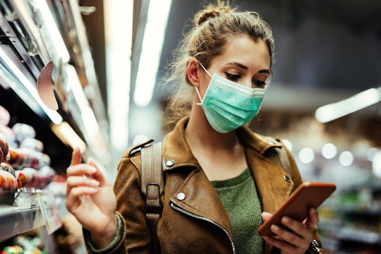 Woman with face mask going through check list on smart phone while buying in supermarket.