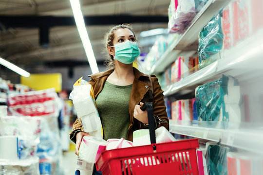 Woman with protective face mask buying toilet paper in the store during virus epidemic.