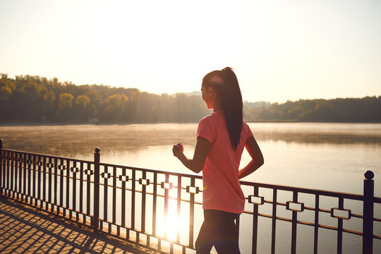 Back view of a runner walking on a road in a park