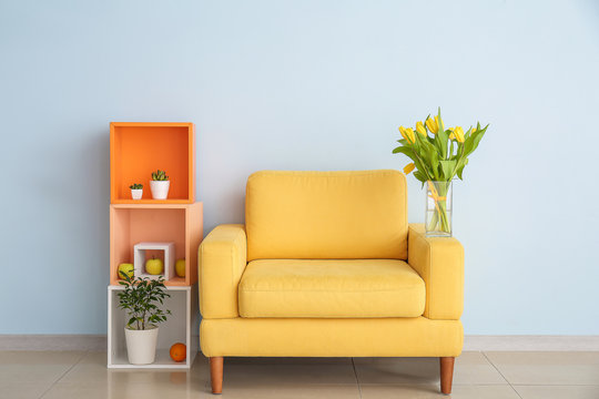 Interior of modern room with comfortable armchair, shelf unit and spring flowers near light wall