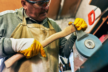 Image of adult craftsman manufacturing in his workshop. Mature worker man grinding the hatchet with sparks in repair shop.