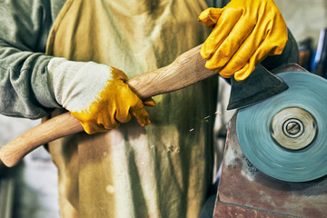 Poster Closeup shot of an adult craftsman manufacturing in his workshop. Professional senior worker man grinding the hatchet with sparks in repair shop.
