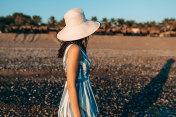 Side view image of brunette beautiful woman with white hat, walking along the beach at seaside on the sunset background. Female wearing striped dress posing outside during vacation. Travel concept.