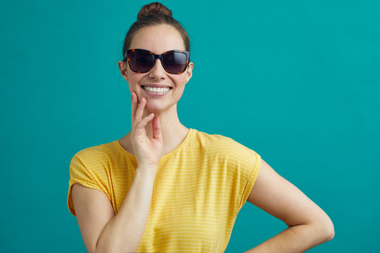 Beautiful woman wearing sunglasses, in a bright yellow shirt on a contrast background
