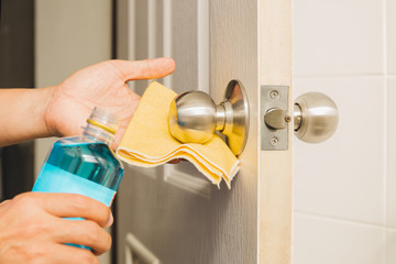 Hand cleaning door knob with alcohol and yellow microfiber cloth.