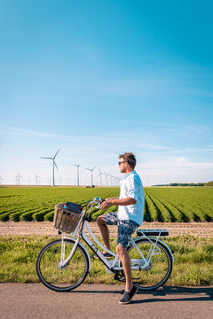 young man electric green bike bicycle by windmill farm , windmills isolated on a beautiful bright day Netherlands Flevoland Noordoostpolder