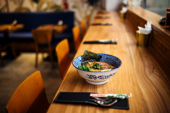 Delicious hot warming japanese ramen noodles soup in a traditional blue bowl on the table, horizontal