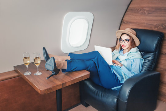 An Asian girl is flying on a plane in business class and drinking a glass of champagne, while working on a notebook online