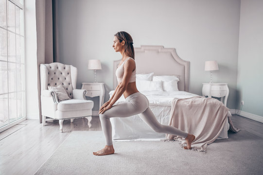 Home fitness. Young sporty fit slim woman doing morning work-out yoga exercises in bedroom at self isolation quarantine. COVID-19 concept to promote stay safe home save lives. Healthy body lifestyle