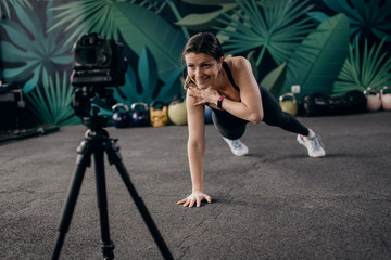 Young female fitness instructor making online training. Young fitness instructor shows how to exercise at home.