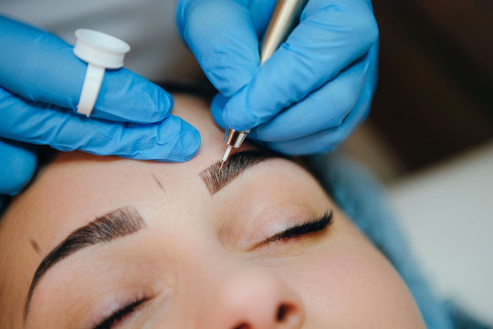 Permanent make-up for eyebrows of beautiful brunette woman in beauty salon. Closeup beautician in gloves doing microblading for eyebrow.