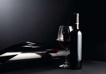 Poster Vin Bottle and glass of red wine on a dark background.