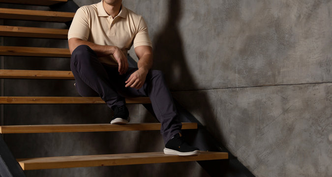 Man at home in blank polo shirt . Sitting on the stairs near the wall at home. Mockup for print