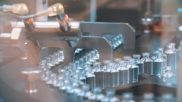 Glass bottles in production in the tray of an automatic liquid dispenser, a line for filling medicines against bacteria and viruses, antibiotics and vaccines.
