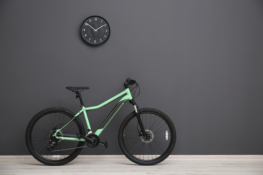 Modern green bicycle near grey wall indoors. Space for text