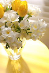 Beautiful bouquet with fresh freesia flowers in vase on table near window