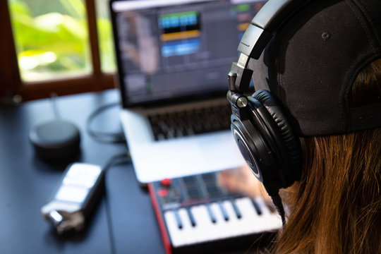 Close up of a female music producer with headphones in her home studio, desk with digital recorder, Smart Home Assistant, notebook and a Midi keyboard. Window with nature in the background.