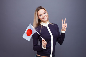 Immigration and the study of foreign languages, concept. A young smiling woman with a Japan flag in her hand.